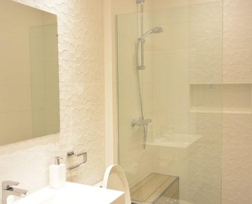 La céramique de murale texturée derrière le meuble lavabo est rappelée en insertion verticale dans la douche ainsi qu'au fond de la niche de douche servant à déposer les savons et bouteille de shampoing.Salle de bain lumineuse, douche à l'italienne et plancher chauffant.