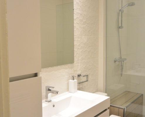 Salle de bain avec douche à l'italienne à Québec. Meuble lavabo blanc lumineux vasque intégré aux ligne épurée. Dosseret de porcelaine texturé blanc.