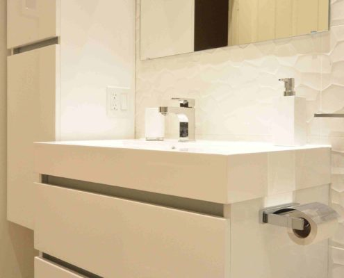 Meuble lavabo blanc lumineux vasque intégré aux ligne épurée. Dosseret de porcelaine texturé blanc.