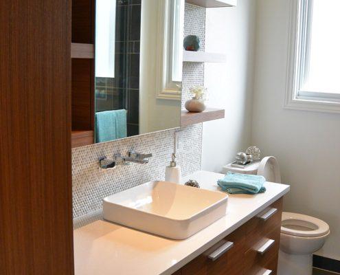Comptoir de quartz, céramique murale, dosseret mosaique, robinetterie murale, porte d'armoire grain horizontal ambrées, FEXA Rénovation Salle de bain épurée