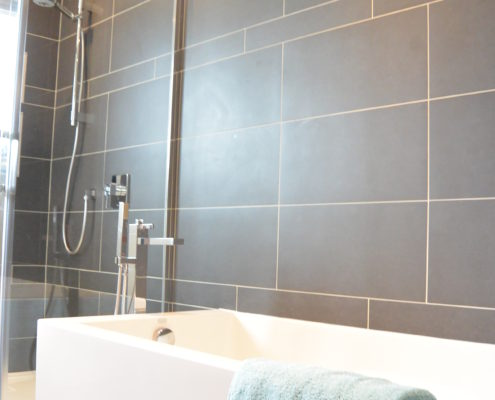 Installation céramique anthracite, céramique murale, bain en coin, douche parapluie, robinetterie sur pied, FEXA Rénovation salle de bain
